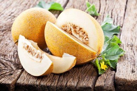 Photo pour Melons mûrs avec des feuilles de melon sur fond en bois . - image libre de droit