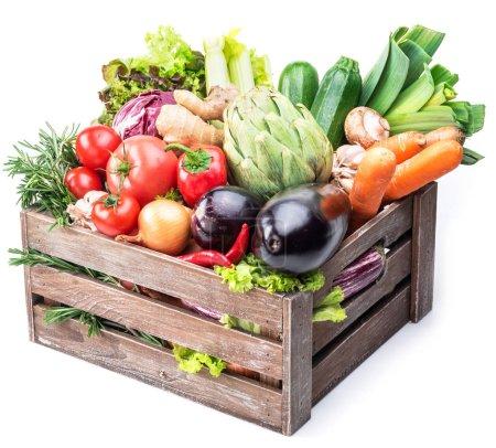 Photo pour Légumes frais multicolores dans une caisse en bois. Fond blanc . - image libre de droit