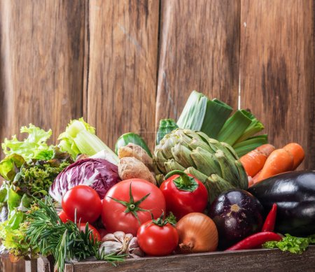 Photo for Fresh multi-colored vegetables in wooden crate. Wooden background. - Royalty Free Image