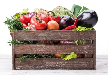 Fresh multi-colored vegetables in wooden crate. White background.