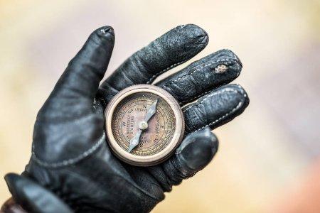 Photo pour Main d'homme dans un gant de cuir tenant une boussole. Contexte naturel . - image libre de droit