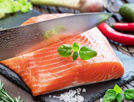 Photo pour Filet de saumon frais sur planche à découper noire aux herbes et épices . - image libre de droit