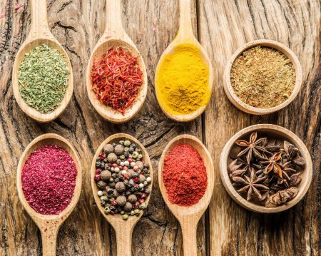 Assortment of colorful spices in the wooden spoons on the old table.