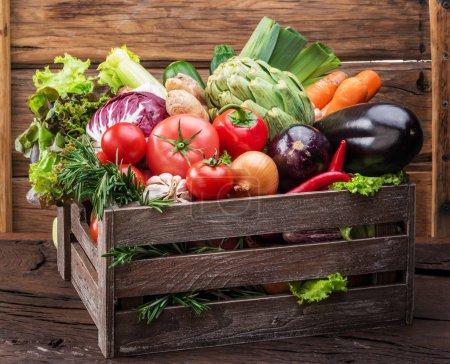 Photo pour Légumes frais multicolores dans une caisse en bois. Fond en bois . - image libre de droit