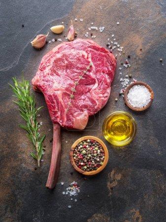 Photo pour Steak de Ribeye cru ou steak de bœuf sur la planche à découper en graphite avec des herbes et des épices. Vue du dessus . - image libre de droit
