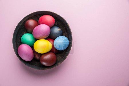 Photo pour Œufs de Pâques colorés comme un attribut de la célébration de Pâques sur l'assiette. Vue du dessus . - image libre de droit
