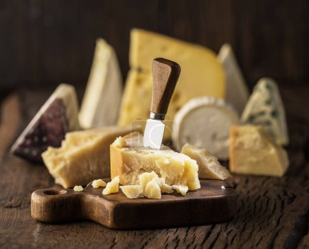Photo for Piece of Parmesan cheese  on the wooden board. Assortment of different cheeses at the background. - Royalty Free Image