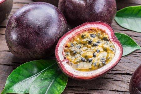 Photo pour Fruits de la passion et sa section transversale avec du jus pulpeux rempli de graines. Fond en bois . - image libre de droit