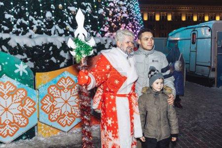 Photo pour Le 24 décembre 2018 - Minsk, Biélorussie : Fêtes de rue dans la ville du soir. Père Noël avec des gens près de l'arbre de Noël - image libre de droit