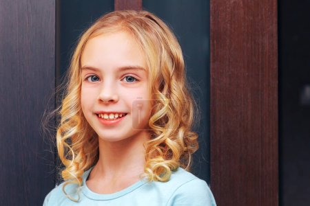 Photo for Beautiful young girl with blond hair is standing indoors - Royalty Free Image