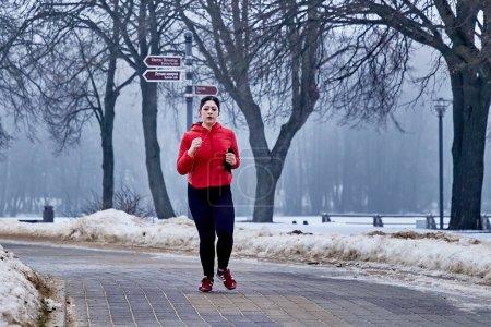 Photo pour 9 février 2019 Minsk Biélorussie Course dédiée au 14 février Une femme court en hiver dans un parc urbain - image libre de droit