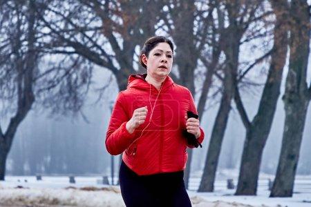 Foto de Febrero 9, 2019 Minsk Bielorrusia Run dedicada al 14 de febrero Primer plano una mujer activa corre en invierno en el parque de la ciudad - Imagen libre de derechos