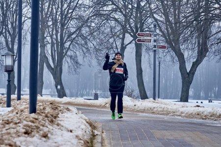 Foto de Febrero 9, 2019 Minsk Bielorrusia Run dedicado al 14 de febrero Un hombre feliz con una mano levantada corre a lo largo de un camino en un parque en invierno - Imagen libre de derechos