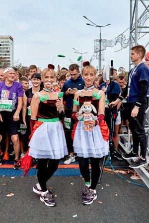 Foto de Septiembre 15, 2019 Minsk Bielorrusia Hay dos mujeres maduras Gemelas con disfraces de carnaval de pie antes del inicio de la maratón - Imagen libre de derechos
