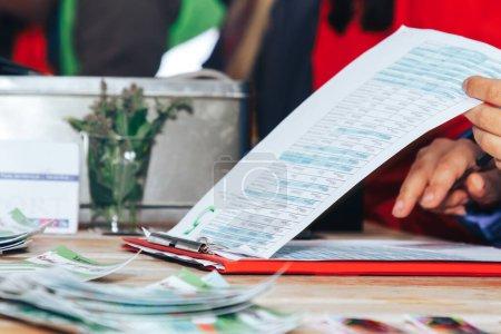 Foto de Primer plano antes del inicio de la carrera nocturna los voluntarios preparan documentos para los participantes - Imagen libre de derechos
