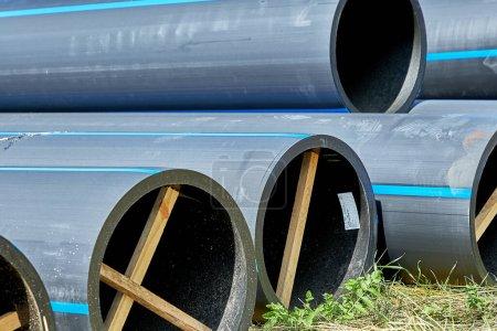 Photo pour Tuyaux sous pression en polyéthylène pour tuyaux d'eau froide avec des jambes en bois pour préserver le diamètre - image libre de droit