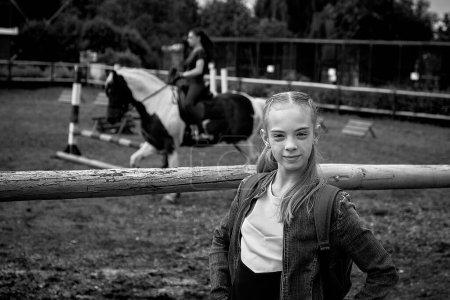 Photo pour 21 juin 2020 Minsk Biélorussie Une belle adolescente se tient à côté d'une volière où une fille est engagée dans des sports équestres à cheval - image libre de droit
