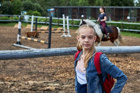 Photo pour 21 juin 2020 Minsk Biélorussie Une adolescente se tient à côté d'une volière où une fille pratique des sports équestres sur un cheval - image libre de droit