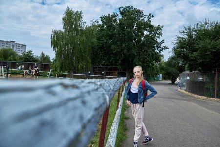 Foto de Junio 21 2020 Minsk Bielorrusia Una hermosa adolescente se para junto a un aviario donde las niñas practican deportes ecuestres a caballo - Imagen libre de derechos