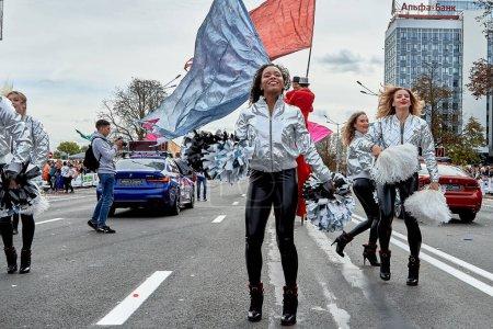 Foto de Septiembre 15, 2019 Minsk Bielorrusia Un grupo de hermosas animadoras con grandes lazos bailando activamente en la carretera antes del inicio de la maratón - Imagen libre de derechos