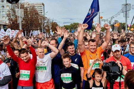Foto de Septiembre 15, 2019 Minsk Bielorrusia Hay muchos participantes felices de la maratón que están de pie con las manos levantadas antes del comienzo - Imagen libre de derechos