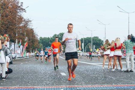 Foto de Septiembre 9, 2018 Minsk Bielorrusia Media Maratón Minsk 2018 Una carrera de maratón en la que un corredor de maratón corre a la meta por delante de los participantes - Imagen libre de derechos