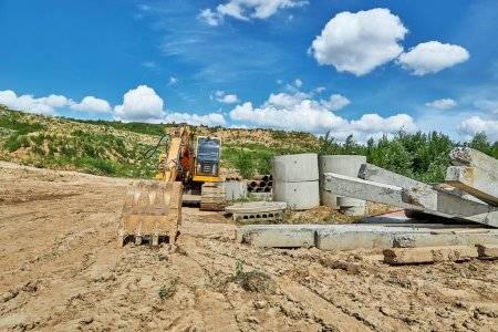 Photo for An excavator stands next to concrete products at a construction site reconstructing an old water supply network - Royalty Free Image