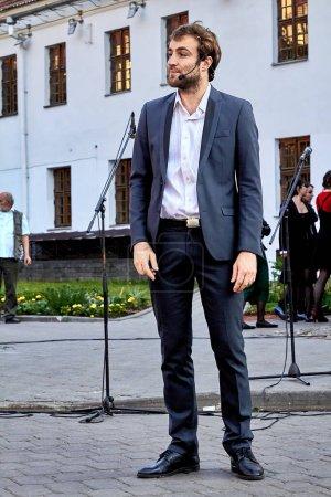 Photo pour 25 mai 2019 Minsk Biélorussie Un bel acteur en costume noir avec une barbe se tient à un concert de rue - image libre de droit