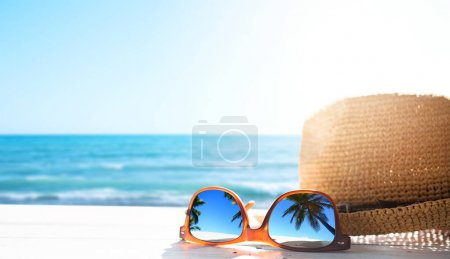 Photo for Summer tropical beach background; glasses and palm tree refle - Royalty Free Image