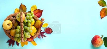 Foto de Thanksgiving background; basket with autumn fresh Fruit and autumn leaves; - Imagen libre de derechos