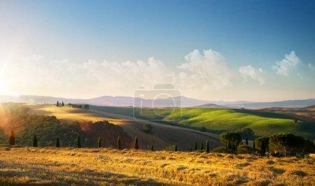 Foto de Puesta de sol sobre el paisaje paisajístico de la Toscana de otoño; colinas ondulantes y villag - Imagen libre de derechos