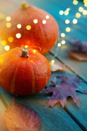 Foto de Autumn pumpkin and holidays light decoration on wooden table; thanksgiving holiday party background, - Imagen libre de derechos