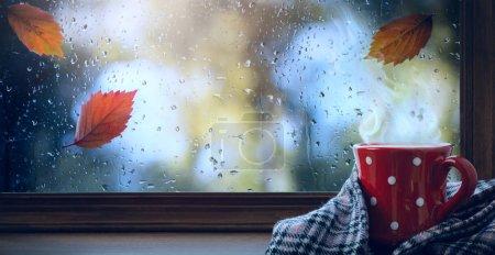 Foto de Red cup with hot drink and wet autumnal window; Autumn season background - Imagen libre de derechos