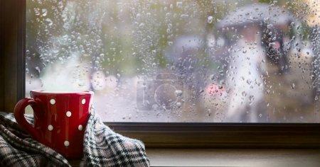 Foto de Fondo de temporada de otoño, taza roja con bebida caliente y ventana otoñal húmeda - Imagen libre de derechos