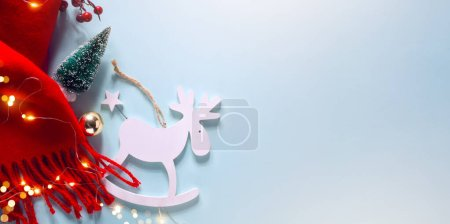 Foto de Christmas blue light background with Xmas sparkling lights garland and Christmas tree decoration, top view, copy space. Horizontal Christmas poster, greeting cards, headers, website banne - Imagen libre de derechos