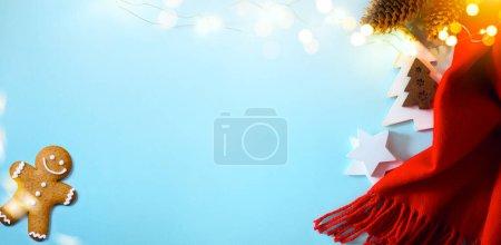 Foto de Christmas blue background. White winter scarf and holiday decoration top view. Happy New Year card. - Imagen libre de derechos