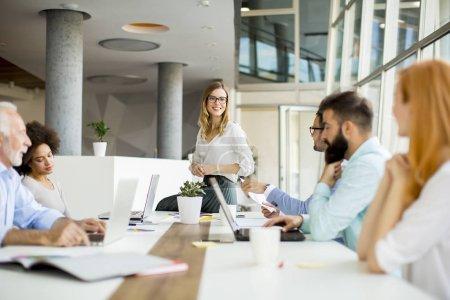 Photo pour Vue multiraciale des gens d'affaires autour de la table lors du personnel réunion et souriant - image libre de droit