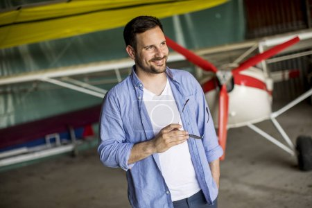 Photo pour Beau jeune homme dans le hangar d'avion - image libre de droit
