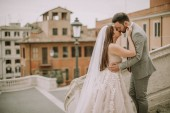 """Постер, картина, фотообои """"Young attractive newly married couple posing in Rome with beautiful and ancient architecture in the background"""""""