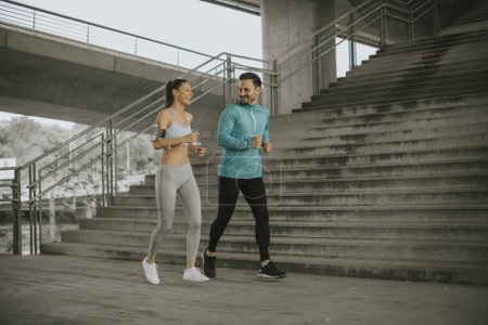 Photo for Young couple running in the urban enviroment - Royalty Free Image