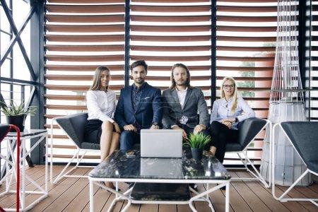 Photo pour Groupe de jeunes gens dans les bureaux modernes ont équipe de rencontre et de réflexion tout en travaillant sur l'ordinateur portable au bureau moderne - image libre de droit