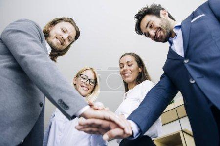 Photo pour Gros plan de jeunes collaborateurs, mettre les mains ensemble en tant que symbole de l'unité dans le Bureau - image libre de droit