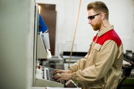 Photo pour Beau jeune homme travaillant à la machine dans l'usine - image libre de droit
