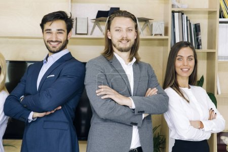 Portrait of friendly businesspeople in suits standing at office