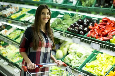 Young woman buying vegetables in the supermarket