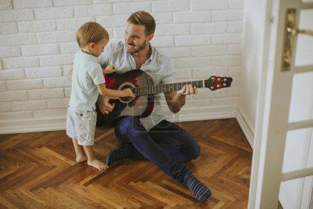 Photo pour Père et fils avec guitare à la maison - image libre de droit