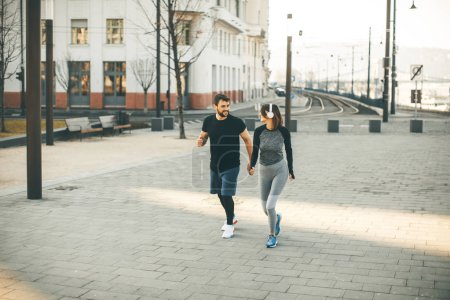 Photo for Healthy young couple running in the city with cityscape in background - Royalty Free Image
