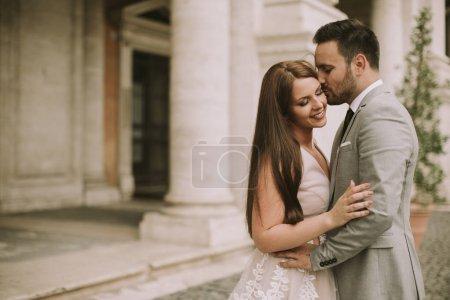 Photo pour Jeune beau couple nouvellement marié posant à Rome avec belle et ancienne architecture en arrière-plan - image libre de droit