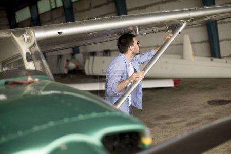 Photo pour Beau jeune pilote vérifiant l'avion dans le hangar - image libre de droit