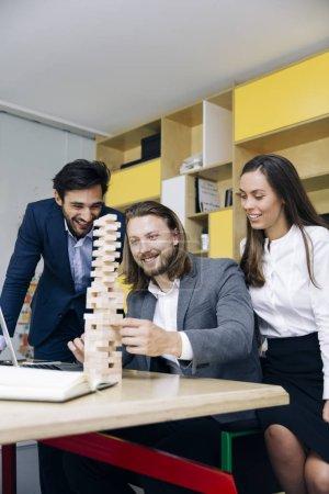 Photo pour Une équipe de jeunes entrepreneurs construit une construction en bois dans le bureau - image libre de droit